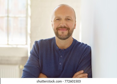Smiling relaxed friendly middle-aged man with a beard leaning against a white interior wall with folded arms