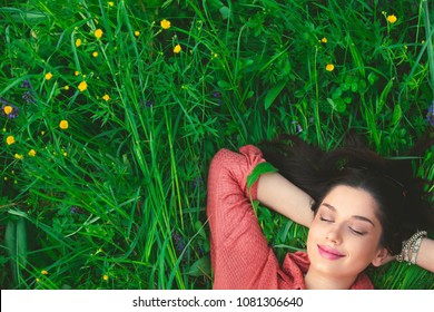 Smiling relaxed woman lying in grass with hands under the head with copy-space for text