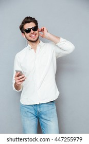 Smiling relaxed young man in sunglasses listening to music from mobile phone over grey background