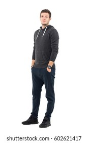 Smiling relaxed young sportive man in hooded sweatshirt with hands in pockets. Full body length portrait over white studio background.