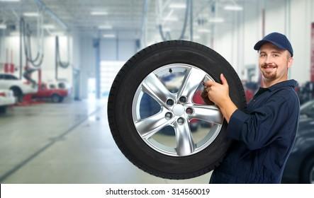 Smiling repairman with tire a in car repair service.