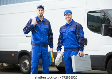 Smiling Repairman With Toolbox And Cable Standing In Front Of Vehicle