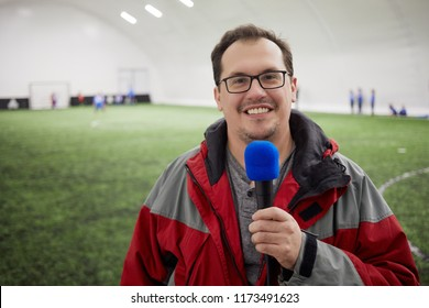 Smiling reporter with microphone on covered sports ground.