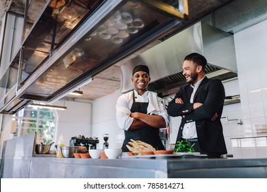 Smiling restaurant owner and chef standing in kitchen. Businessman with professional cook standing together and laughing.