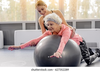Smiling retiree leaning on fitball