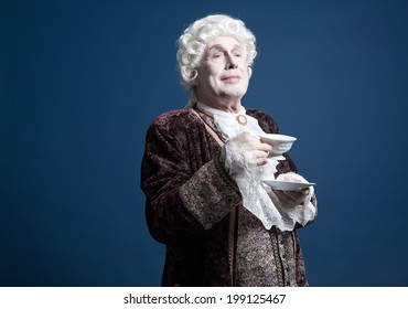 Smiling retro baroque man with white wig holding a porcelain tea cup. Studio shot against blue.