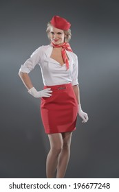 Smiling retro blonde stewardess wearing red skirt and cap with white shirt. Studio shot against grey.