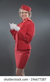 Smiling retro blonde stewardess wearing red suit with cap. Holding cup of coffee. Studio shot against grey.