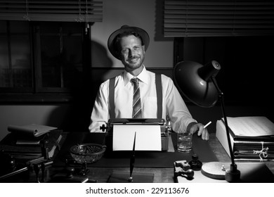 Smiling retro reporter having a cigarette break at desk.