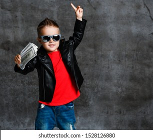 Smiling rich kid boy in sunglasses and leather jacket with a bundle of money dollars cash holding his finger up showing First sign on concrete wall background with free copy space
