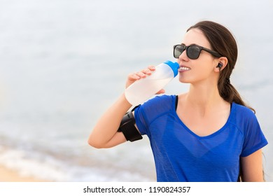 smiling runner woman drinks water from bottle and listen to music in earphones on the sea beach