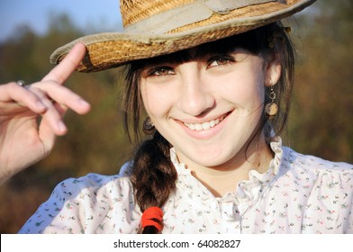 Smiling rural girl with straw hat
