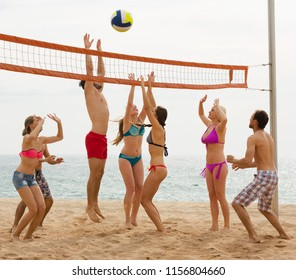 smiling russian adults throwing ball over net and laughing