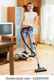 smiling russian middle-aged woman hoovering apartment