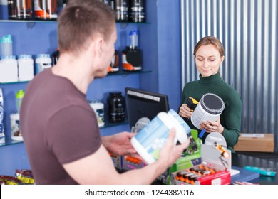 Smiling salesgirl counseling young athletic man about sport nutritional supplements