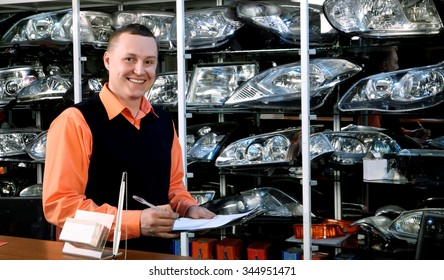 Smiling Salesman Auto Parts Store with a Notebook in Hand