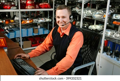 Smiling Salesman Auto Parts Store with a Computer