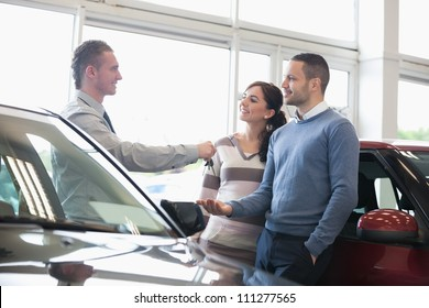 Smiling salesman handing keys to a couple in a car shop