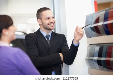 Smiling salesman pointing at a color palette with a woman
