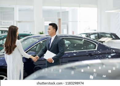 Smiling salesman and pretty female client shaking hands in car showroom