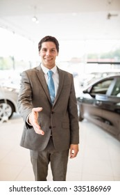 Smiling salesman ready to shake hand at new car showroom