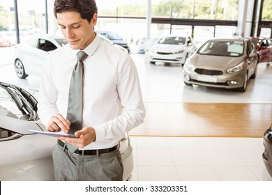 Smiling salesman using tablet near a car at new car showroom