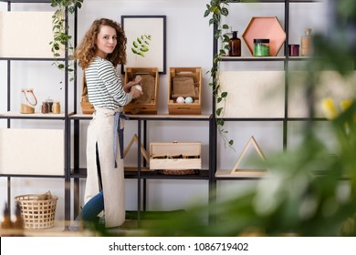 Smiling saleswoman arranging natural healthcare products on wooden boxes in the shop