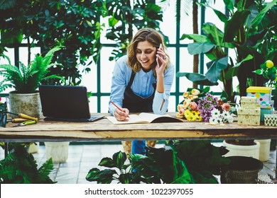 Smiling saleswoman in floral retail shop talking on mobile phone with client noting order for bouquet at desktop,female gardener in apron communicating during telephone conversation about delivery