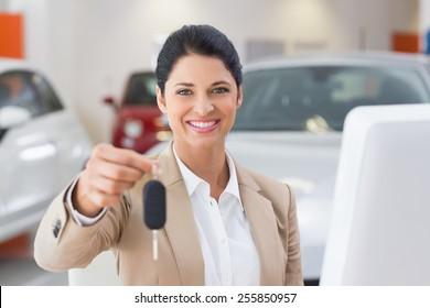 Smiling saleswoman giving a customer car key at new car showroom