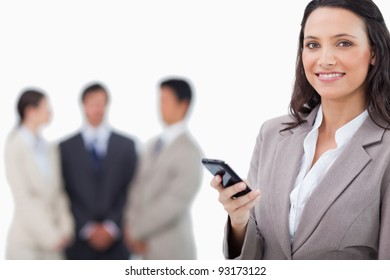 Smiling saleswoman holding cellphone with team behind her against a white background