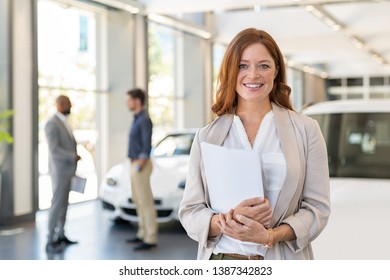 Smiling saleswoman holding document while looking at camera at car showroom. Cardealer holding clipboard in automobile showroom. Professional confident sales person working in modern car dealership.