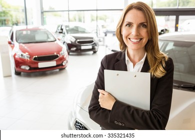 Smiling saleswoman holding document while looking at camera at new car showroom
