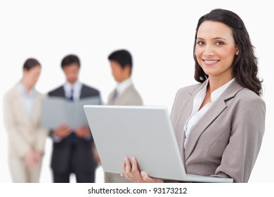 Smiling saleswoman with laptop and colleagues behind her against a white background