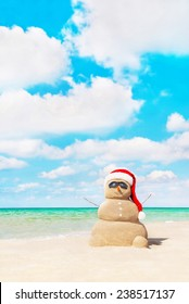 Smiling sandy snowman in red santa hat at tropical beach. New Years and Christmas holidays in hot countries concept