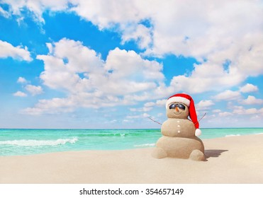 Smiling sandy Snowman in red Santa hat and sunglasses at sunny tropical beach. New Year and Christmas concept for travel destinations in hot tourist countries