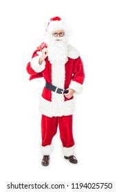 smiling santa claus in eyeglasses holding christmas sack over shoulder isolated on white background