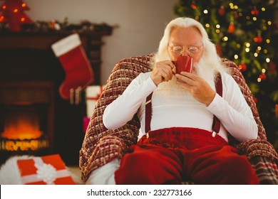 Smiling santa holding cup of coffee at home in the living room