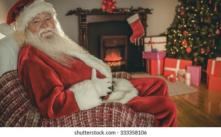 Smiling santa sitting and holding his belly at home in the living room