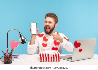 Smiling satisfied man with beard in white shirt covered with sticky hearts showing thumbs up holding smartphone with empty display. Indoor studio shot isolated on blue background