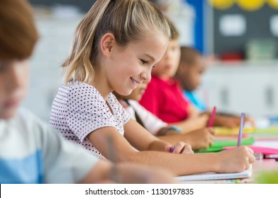 Smiling scholar girl sitting with other children in classroom and writing on textbook. Happy student doing homework at elementary school. Young schoolgirl feeling confident while writing on notebook.