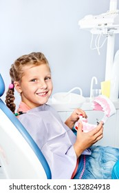 Smiling school aged girl cleaning toy dentures with a toothbrush