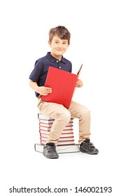 Smiling school boy sitting on a pile of books and reading isolated on white background