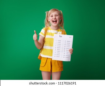 smiling school girl with backpack with an excellent grade test showing thumbs up against green background