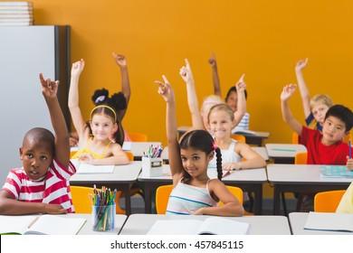 Smiling school kids raising hand in classroom at school