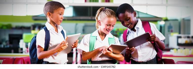 Smiling school kids using digital tablet in cafeteria at school