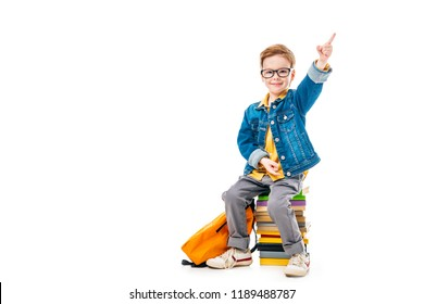 smiling schoolboy pointing up while sitting on pile of books with backpack, isolated on white