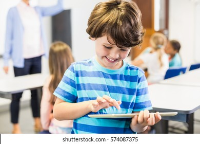 Smiling schoolboy using digital tablet in classroom at elementary school