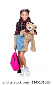 smiling schoolchild holding teddy bear and backpack isolated on white