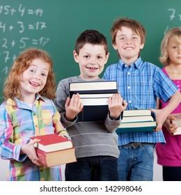 Smiling schoolchildren holding books in front of blackboard