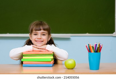 smiling schoolgirl in the classroom on the background of chalkboard,